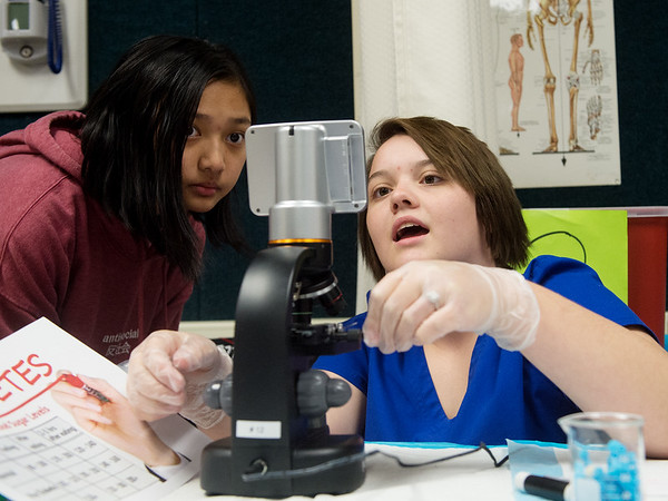 Chalynn Bogenrief, senior at Neosho High School, shows Sienna Yang, eighth grader at Neosho Junior High School, blood under a microscope on Tuesday at the Dell Reed Technical Education Center at Crowder College.<br /> Globe | Roger Nomer