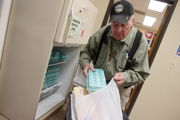 George Graham volunteers in the food pantry at Wesley House on Monday. The Empty Bowls fundraiser will benefit the food pantry.<br /> Globe | Roger Nomer
