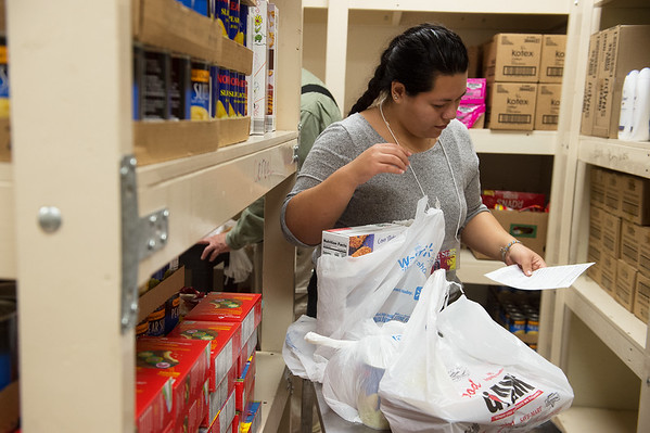Zaira Gomez, a Pittsburg State University sophomore from Kansas City, Kan., volunteers in the food pantry at Wesley House on Monday. The Empty Bowls fundraiser will benefit the food pantry.<br /> Globe | Roger Nomer