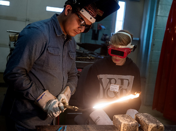 Michael Segura, senior at McDonald County High School, demonstrates a welding torch for Anthony Stephens, eighth grader at Neosho Junior High School, on Tuesday at the Dell Reed Technical Education Center at Crowder College.<br /> Globe | Roger Nomer