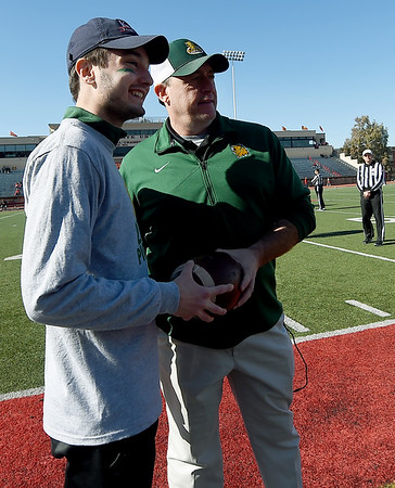 From the left: Missouri Southern Kappa Alpha President Rylee Hartwell presents a ceremonial game ball from the 2019 Pigskin Run to MSSU Coach Jeff Sims at Carnie Smith Stadium before the start of the Pittsburg State/MSSU football game. The ball was later given to MDA ambassador MiKayla Berry. <br /> Globe | Laurie SIsk