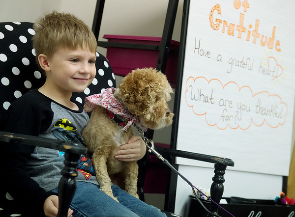 Uriah Friend, kindergartner at Royal Heights Elementary, poses for a photo with Bridget as a reward for knowing letter sounds on Tuesday at the school.<br /> Globe | Roger Nomer