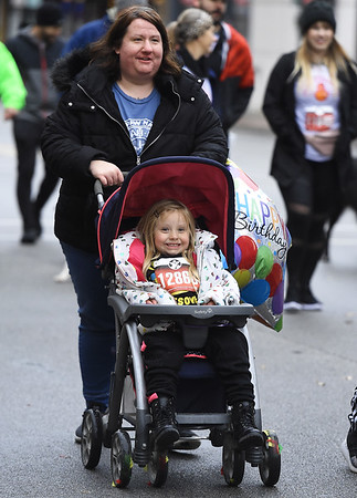 Wet conditions can't wash the smile from Avalynn Nichols face as she celebrates her fifth birthday at the 8th Annual Joplin Turkey Trot on Saturday in downtown Joplin with her mom, Megan Nichols..<br /> Globe | Laurie Sisk