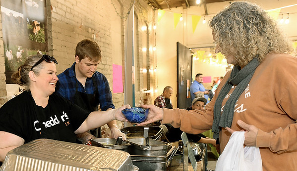 Former Joplin resident Melissa Marcum, right, now of Kansas City, samples a bowl of loaded baked potato soup as Cheddar's volunteer Denise Coots assists during the 2019 Watered Gardens Empty Bowls Project on Thursday at Empire Market. Marcum was celebrating her birthday with a trip from Kansas City to attend the event, which she has long supported. Proceeds from the event go to battle hunger in the area.  Also pictured is Watered Gardens employee Jack Girard.<br /> Globe | Laurie Sisk