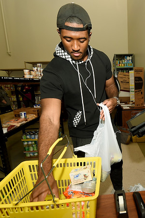 Missouri Southern student Jamal Tasfay shops at the Lion Co-op on Wednesday. The co-op, formed last year, is starting a new program called Adopt A Lion, in which donors may sponsor a lion throughout the month of December to ensure that they'll have food over Christmas break.<br /> Globe | Laurie Sisk