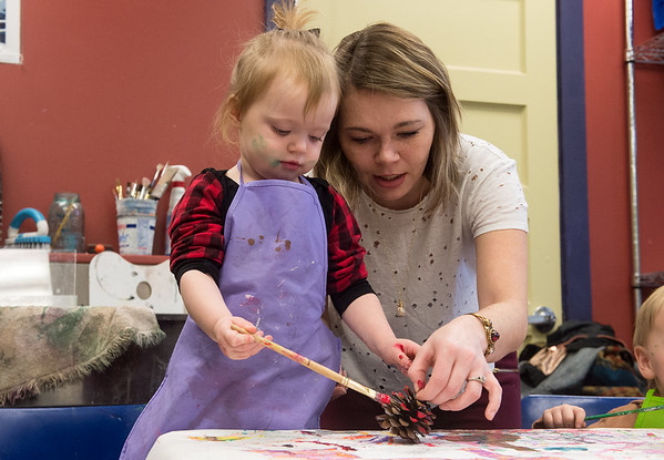 Samantha Smith helps her daughter Ryder Blanton, 1, decorate a pinecone during the Black Friday Make and Take class at Spiva Center for the Arts. <br /> Globe | Roger Nomer