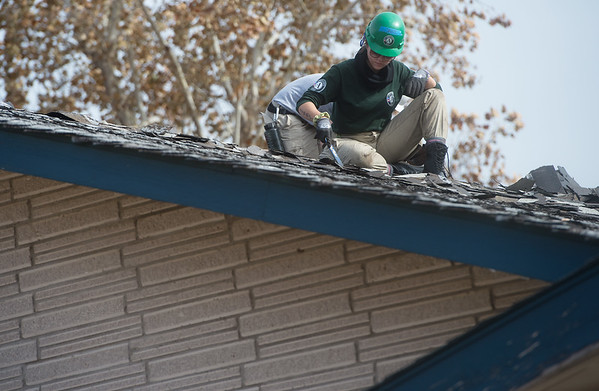Dani Hodge, from Raleigh, N.C., works on a roof at Royal Heights Baptist Church on Monday during an Americorps project.<br /> Globe | Roger Nomer