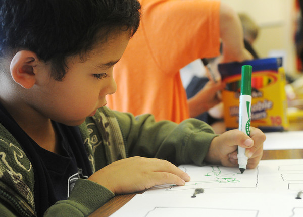 Globe/Roger Nomer<br /> Teigan Vallejo, a kindergartner at West Central Elementary, works on his comic book in art class on Wednesday.