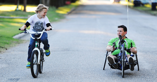 Brian Smith (right), races his 10-year-old son, Nick Smith, down a road Wednesday evening, Oct. 9, 2013, near their Baxter Springs, Kan., home. Smith is a paraplegic preparing for the Mother Road Marathon.<br /> Globe | T. Rob Brown