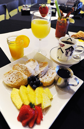 Artisan french toast (foreground) from the brunch menu at Club 1201, located at 1201 E. 32nd St., Joplin. Also pictured are (clockwise from left) orange juice, a mimosa, a bloody Mary from the bloody Mary bar (background) and a cup of coffee.<br /> Globe | T. Rob Brown