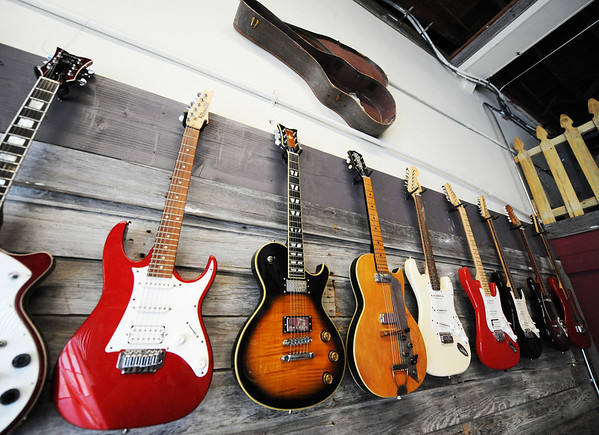 A row of electric guitars hang on the wall at Wood & Wire Guitars Wednesday morning, Oct. 2, 2013, in the downtown Joplin business.<br /> Globe | T. Rob Brown
