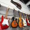 A row of electric guitars hang on the wall at Wood & Wire Guitars Wednesday morning, Oct. 2, 2013, in the downtown Joplin business.<br /> Globe   T. Rob Brown