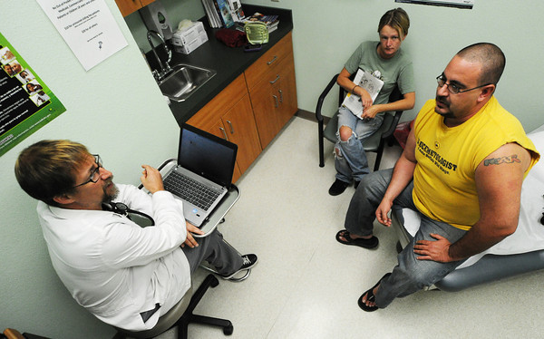 Nurse practitioner Todd Carl (left) speaks with patient James Fearmonti (right) and wife Jessie Fearmonti, both of Frontenac, Wednesday morning, Oct. 9, 2013, at the Community Health Center of Southeast Kansas in Pittsburg.<br /> Globe | T. Rob Brown