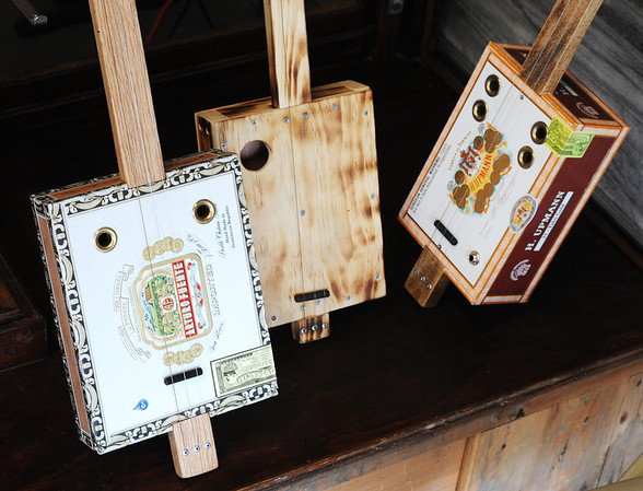 Homemade cigar box guitars and one wooden box guitar.<br /> Globe | T. Rob Brown