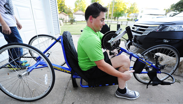 Brian Smith, a paraplegic preparing for the Mother Road Marathon, gets into his sports bicycle Wednesday evening, Oct. 9, 2013, at his Baxter Springs, Kan., home.<br /> Globe | T. Rob Brown