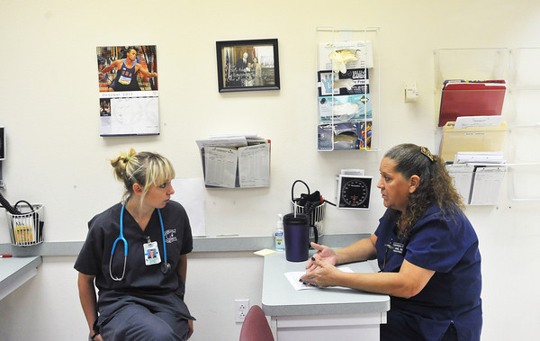 Globe/Roger Nomer<br /> Jane Fillmore, RMA at the community clinic, right, gives an orientation talk to Lacy Harrington, a nursing student from Crowder, on Harrington's first day at the clinic on Wednesday.