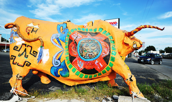 "This plaster bull, bearing a Mexican-style paint scheme, appears to be ""playing chicken"" with automobiles as they turn into a parking lot Friday afternoon, Oct. 4, 2013, on West 7th Street, near South Connor Ave.<br /> Globe 
