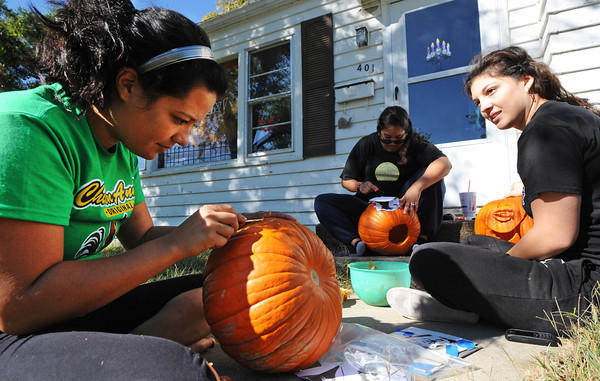 Marisa Ortiz (left) creates a Batman jack-o-lantern as her roommate Erica Gutierrez (center) cuts a raven pattern and her sister Nicole Ortiz creates a vampire pumpkin Saturday afternoon, Oct. 19, 2013, in Pittsburg, Kan.<br /> Globe | T. Rob Brown