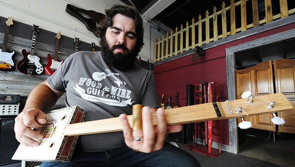 Dan McCain, owner of Wood & Wire Guitars, plays a homemade cigar box guitar Wednesday morning, Oct. 2, 2013, in his downtown Joplin business.<br /> Globe | T. Rob Brown