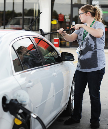 """Valerie Roberts of Joplin cleans her windshield as she fills the tank Thursday afternoon, Oct. 3, 2013, at the Fastrip on Duquesne Road, just north of Missouri Southern State University. """"We haven't seen it like that in a while,"""" Roberts said of the drop below $3 a gallon.<br /> Globe 