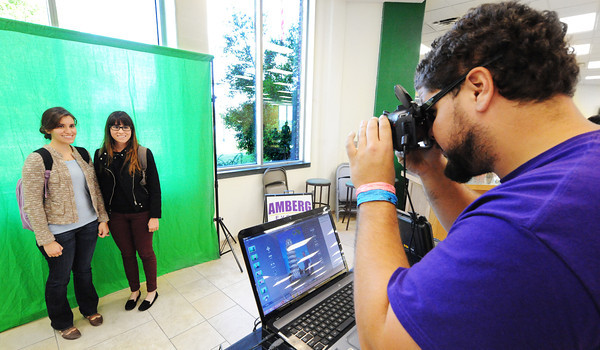 Sisters freshman Diana Aguinaga (left) and senior Stephany Aguinaga pose for a green-screen photo in front of a digital Tower of Pisa Wednesday afternoon, Oct. 23, 2013, in the Billingsly Student Center at MSSU. D.J. Brito of New Jersey (right), a student at Evangel and an Amberg Events staff photographer takes the sisters' photo as part of the Campus Activities Board-sponsored event.<br /> Globe | T. Rob Brown