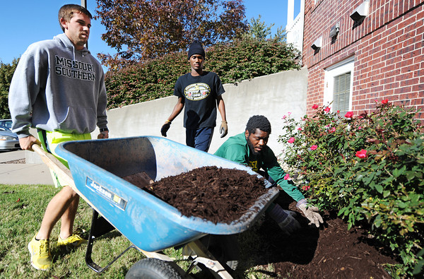 MSSU track team members (from left) Zach Williams, junior accounting major and javelin thrower, Clark Tanksley, senior speech communication major and high jumper and 400-meter runner, and Lynzel Owens, freshman psychology major and shotput thrower, volunteer time to do some landscaping Wednesday afternoon, Oct. 23,2013, at the Ronald McDonald House in Joplin.<br /> Globe | T. Rob Brown
