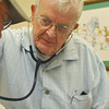 Globe/Roger Nomer<br /> Donald Patterson gives an exam to a patient at the Joplin Community Clinic on Tuesday.  Patterson is an 86-year-old general practice physician who volunteers once a week at the clinic.