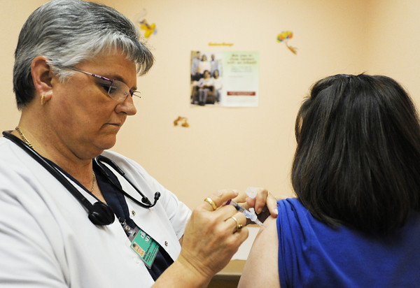 Bette Stansbury (left), patient care, gives a flu shot to patient Crystal Perrin of Frontenac Wednesday morning, Oct. 9, 2013, at the Community Health Center of Southeast Kansas in Pittsburg.<br /> Globe | T. Rob Brown