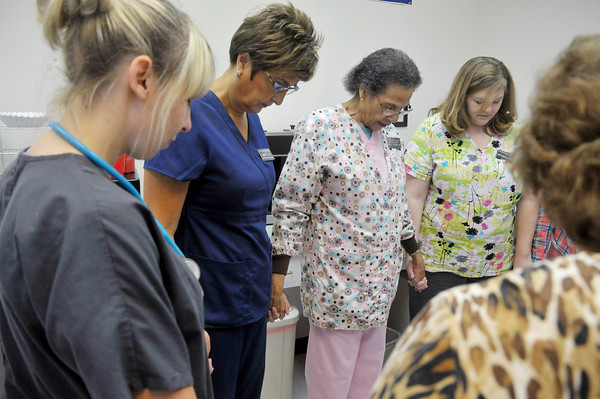 Globe/Roger Nomer <br /> Nurses gather for a morning prayer before the start of the workday at the Joplin Community Clinic on Wednesday morning.  The nurses meet to go over the plans for the day, and say the prayer helps ground them spiritually for coming work.