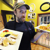Chef Seth Richardson of Joplin holds two plates from the brunch menu, artisan french toast (left) and classic eggs Benedict at Club 1201, located at 1201 E. 32nd St., Joplin.<br /> Globe | T. Rob Brown