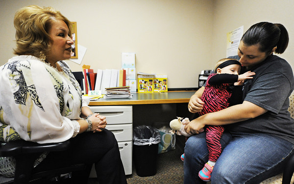 Nine-month-old Brooklin Schoonober reaches up for her mother, Tabatha Schoonober, both of Pittsburg, Kan., as they speak with Krista Smith, registered nurse, Wednesday morning, Oct. 9, 2013, at the Community Health Center of Southeast Kansas in Pittsburg.<br /> Globe | T. Rob Brown