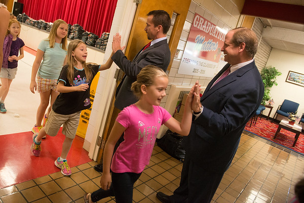 Globe/Roger Nomer<br /> Scott Vorhees, left, and Patrick Martucci receive high-fives from Mark Twain Elementary students on Wednesday in Webb City. The students were saying thank you for the donation of sweatshirts and stocking caps from the attorneys Johnson, Vorhees and Martucci. The law firm annual gives away warm clothing to area students, donating around 2,000 items to students in the Webb City and Neosho districts.