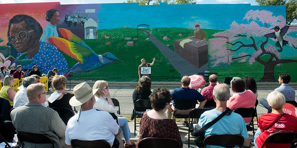 Globe/Roger Nomer<br /> Kyle McKenzie, lead artist on the East Town mural, talks about the design of the mural during Sunday's dedication.