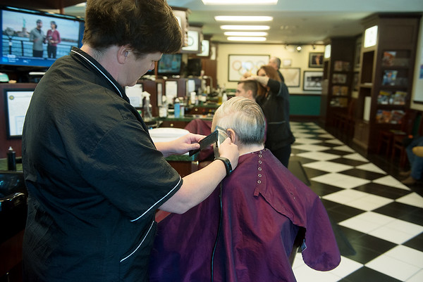 Globe/Roger Nomer<br /> Lori Mayben cuts Larry Albright's hair on Thursday at V's Barber Shop.