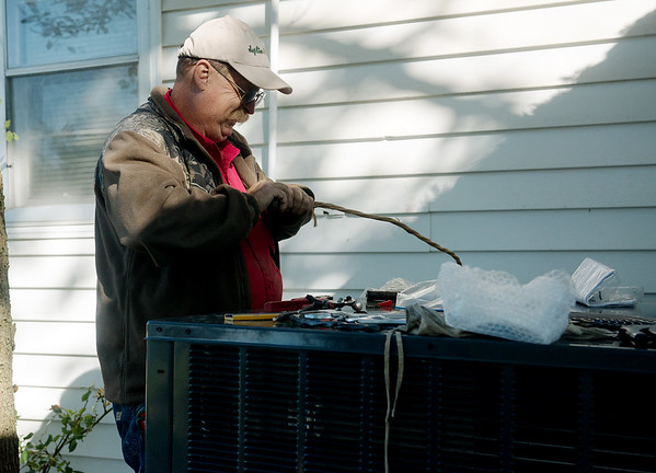 Globe/Roger Nomer<br /> Jim Raven, with Joplin HVAC, installs a gas package unit on Thursday.