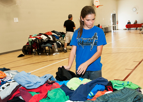 Eleven-year-old Hannah Fehring, of Neosho, checks out items for sale at the Soaring Heights and Eastmorland Elementary schools' benefit rummage sale on Saturday at Soaring Heights. Proceeds from the sale will go to benefit special education programs at both schools.<br /> Globe | Laurie Sisk