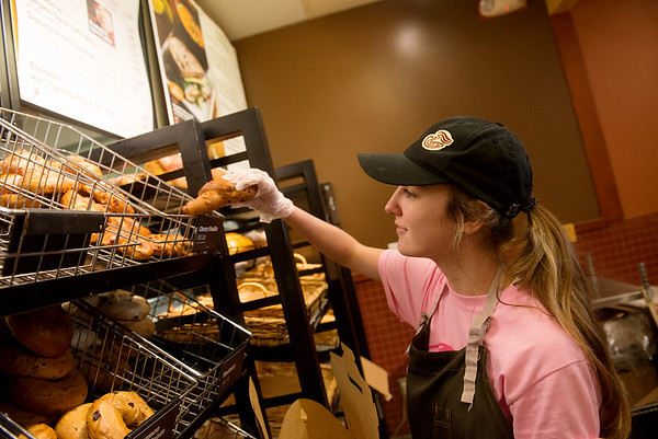 Globe/Roger Nomer<br /> Nicolle Ross serves Pink Ribbon Bagels at Panera on Thursday.