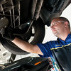 Globe/Roger Nomer<br /> Dustin Jensen works on a car on Thursday at Goodyear Auto Service Center.