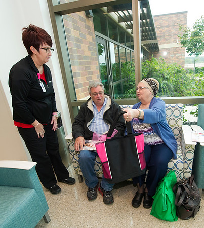 Certified masectomy fitter Lisa Nelson, left, of Sisters Health Boutique inside Mercy Hospital of Joplin, presents breast cancer patient Linda Lacey, of Oronogo, with a gift bag from the boutique as Lacey's husband, Larry Lacey looks on.<br /> Globe | Laurie Sisk