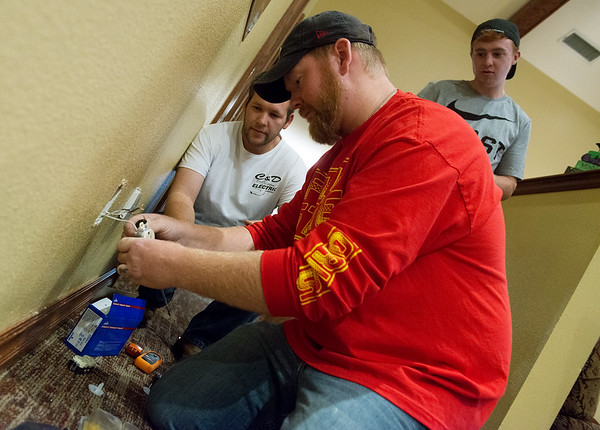 Globe/Roger Nomer<br /> (from left) Clint Myers, with C & D Electric, James McClanahan, a Pittsburg State freshman from Carthage, and Kevin Filby, a freshman from Pittsburg, replace an outlet on Tuesday at the Ronald McDonald House in Joplin. PSU students from the School of Technology volunteered at the house changing its fixtures to LED lighting and doing electrical work.