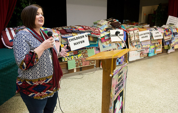 Globe/Roger Nomer<br /> Liz Erickson, development coordinator with Children's Haven, accepts a donation of quilts on Tuesday from the Joplin Area Town and Country Quilters during their meeting at First Presbyterian Church. The agency was one of seven, including Children's Center, Crosslines, Lafayette House, Life Choices, Care Net Pregnancy Resource Center of Neosho, and the Area Agency on Aging, to receive quilts. The quilting group made a total of 178 quilts to be distributed between the charities.