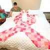 Breast cancer patient Naomi Hunter sits on a quilt handed down to her in her Webb City home.<br /> Globe | Laurie Sisk