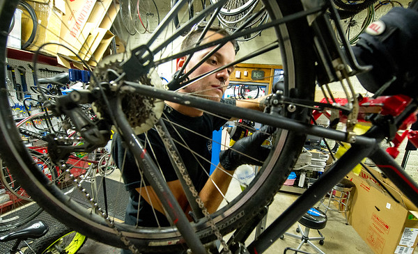 "Blue's Bike Co. mechanic Jake Cornett works on a bike before deprting on a social ""Tuesday 10"" ride on Tuesday night at Blue's Bike Co.<br /> Globe 