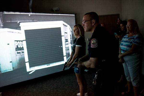 Globe/Roger Nomer<br /> Joplin Assistant Police Chief Maj. Sloan Rowland assists Kacie Smith with a training simulation during a tour of the Public Safety Training Facility on Friday.