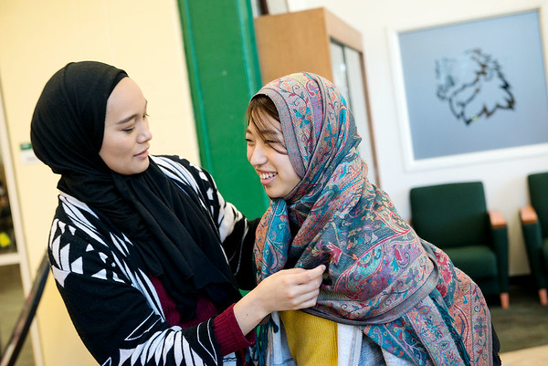Globe/Roger Nomer<br /> Alyssa Stout, a Missouri Southern junior from Nixa, helps Mina Mochizuki, a MSSU exchange student from Japan, with a hijab on Thursday during the Muslim Student Union's Hijab Day at MSSU.