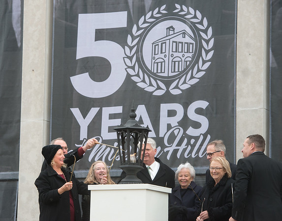 Globe/Roger Nomer<br /> Alan Marble, Missouri Southern president, center, lights a latern for the campus rededication ceremony with families of the university's founding father including (from left) Connie Godwin, Richard Webster Jr., Mary Jane Riggs, Joy Spiva-Cragin, Cobb Young, Linda Cobine and Kurt Ummel on Friday.