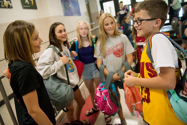 Globe/Roger Nomer<br /> Kelsey Boulware talks with Jacob Linahan as sixth-grade students load backpacks at Pittsburg Middle School on Friday.