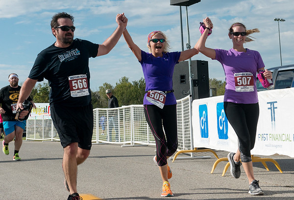Globe/Roger Nomer<br /> Becky Mitchell, Joplin, center, celebrates as she crosses the finish line with her son David Kinnard, Chicago, and daughter Whitney Backsen, Lake of the Ozarks, during the Mother Road Half Marathon on Sunday.