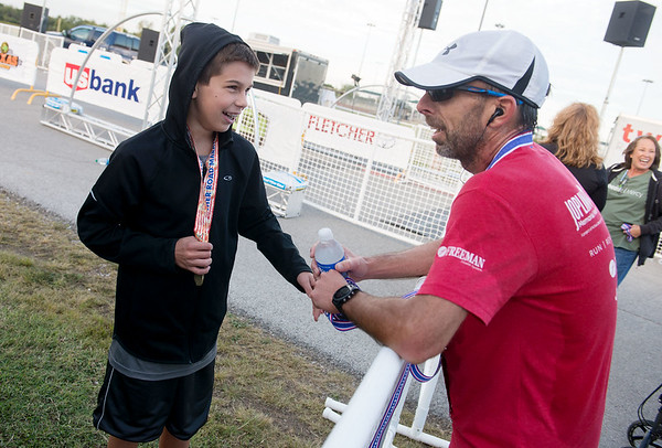 Globe/Roger Nomer<br /> Nate Jennings, 13, Springfield, talks with his dad Ben following the finish of the Mother Road Half Marathon on Sunday. Ben Jennings won the half marathon run, while Nate took first place in his age group in the 5K.