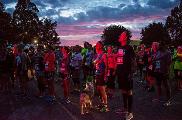 Globe/Roger Nomer<br /> Lit by the lights of their escort police car, runners observe the National Anthem before the start of the Mother Road Half Marathon on Sunday in Baxter Springs.